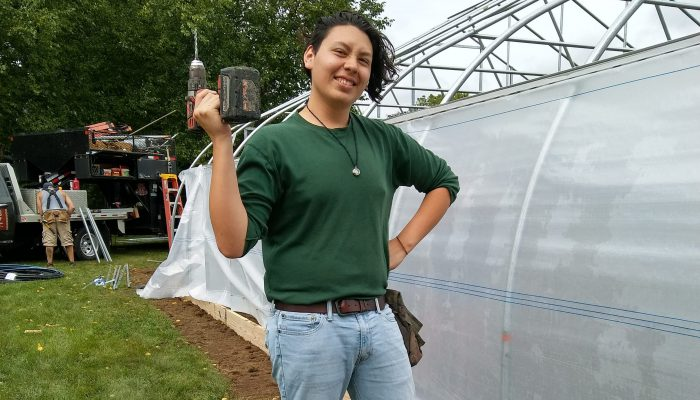 First year student holding a drill at the hoop house build